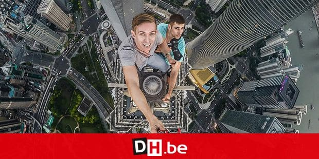 PIC BY ALEX DELARGE/MERCURY PRESS (PICTURED: ALEX DELARGE AND DENIS NEVOZHAI TAKE A SELFIE FROM THE TOP OF THE JIN MAO TOWER IN SHANGHAI, CHINA) This is the moment a daredevil climber scaled one of Chinas tallest skyscrapers - with NO harness or protective clothing. Alex DeLarge filmed himself as he made the nail-biting journey to the top of Shanghais Jin Mao Tower - Chinas third tallest building which stands at a staggering 1380feet (421m). The chilling footage shows Alex as he climbs the ladders to the top of the building wearing a t-shirt, jeans and trainers. Russian-born Alex, who works as a film director in Shanghai, made the journey to the top of the spire with friend Denis Nevozhai, and says the pair could have been deported from China if they had been caught by security staff. SEE MERCURY COPY Reporters / Caters *** Local Caption *** PIC BY ALEX DELARGE/MERCURY PRESS (PICTURED: ALEX DELARGE AND DENIS NEVOZHAI TAKE A SELFIE FROM THE TOP OF THE JIN MAO TOWER IN SHANGHAI, CHINA) This is the moment a daredevil climber scaled one of Chinas tallest skyscrapers - with NO harness or protective