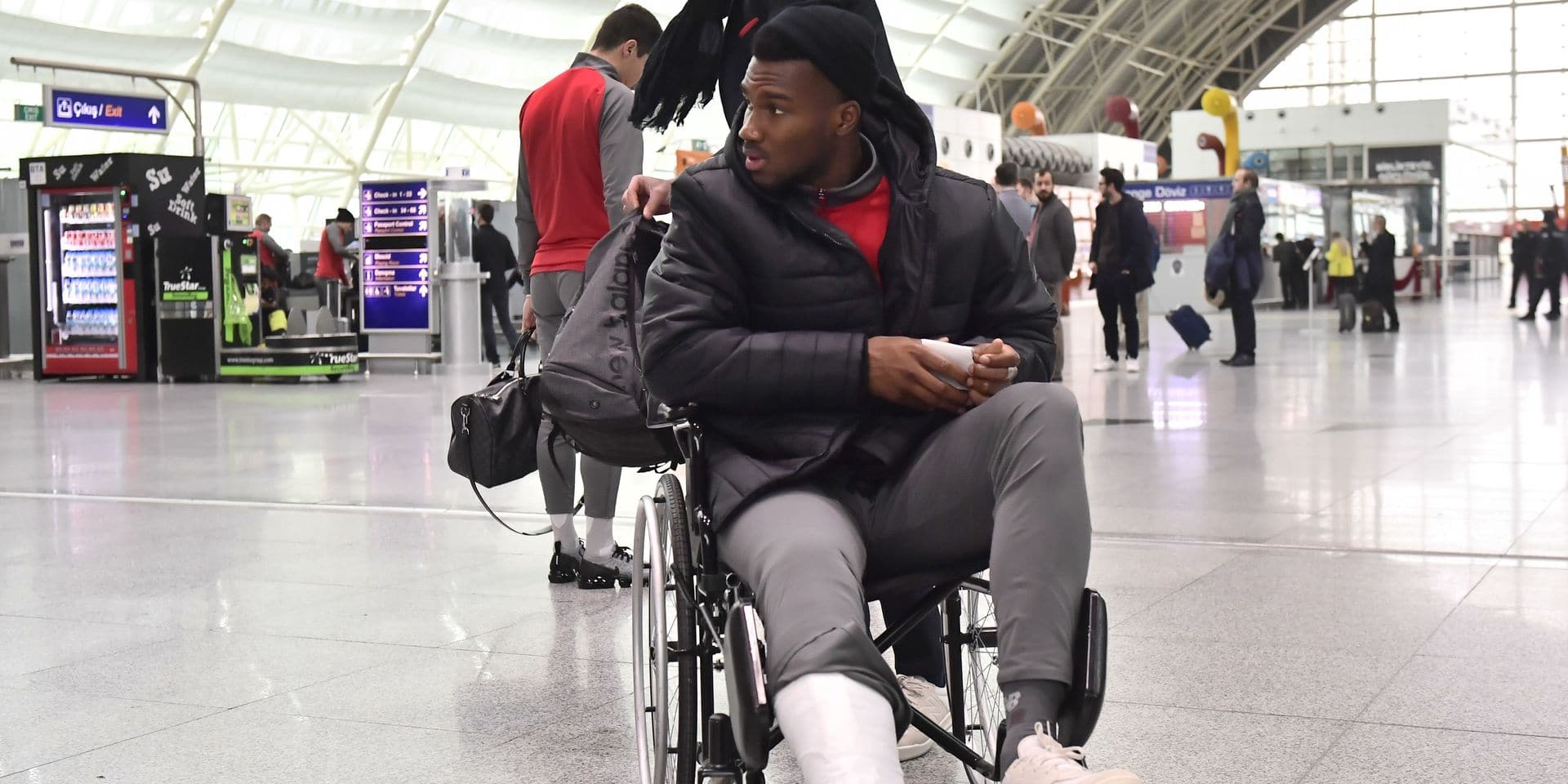 Standard's Obbi Oulare pictured with a plaster cast on his leg, at the airport in Izmir, Turkey Saturday 15 December 2018. Yesterday Belgian soccer team Standard de Liege played Turkish team Akhisar Belediyespor on day six of the Europa League group stage in group J. BELGA PHOTO LAURIE DIEFFEMBACQ