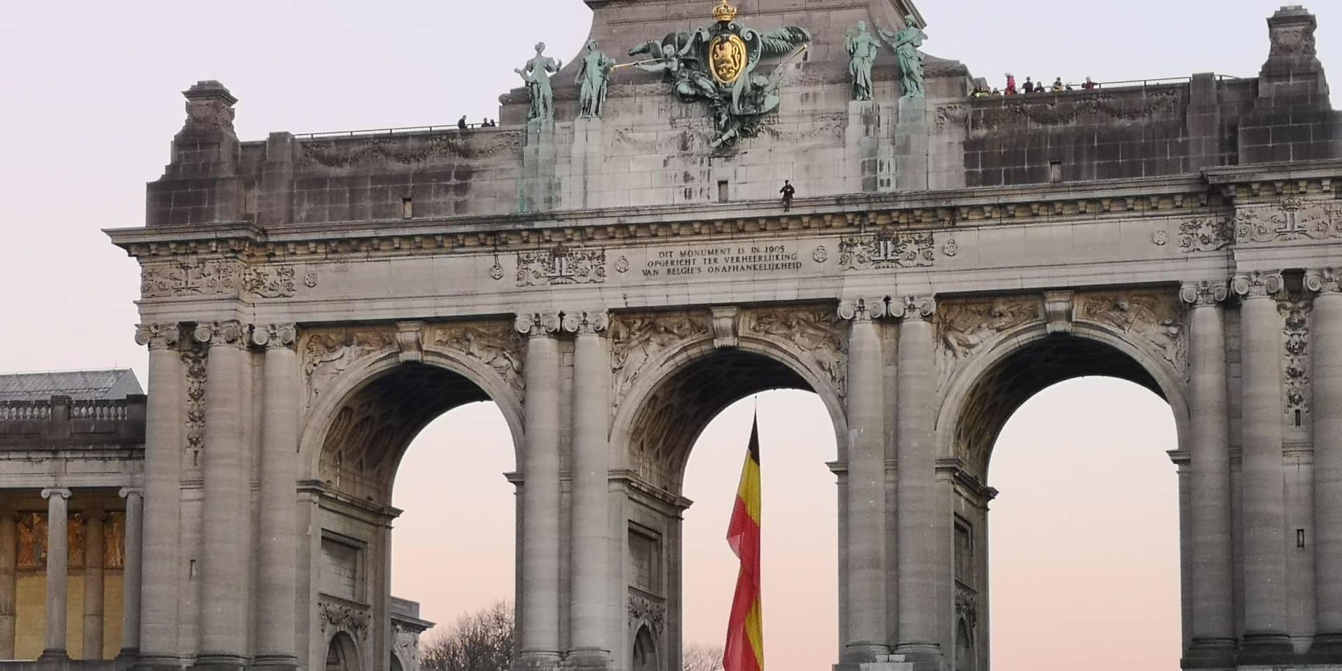 Le Cinquantenaire quadrillé : un homme assis les pieds dans le vide sur les arches