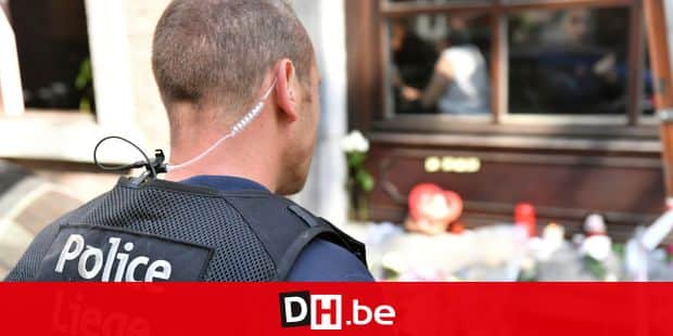 A police officer looks at a flower memorial at the scene of a shooting in Liege, Belgium, Wednesday, May 30, 2018. A gunman killed three people, including two police officers, in the Belgian city of Liege on Tuesday. Police later killed the attacker, and other officers were wounded in the shooting.(AP Photo/Geert Vanden Wijngaert)