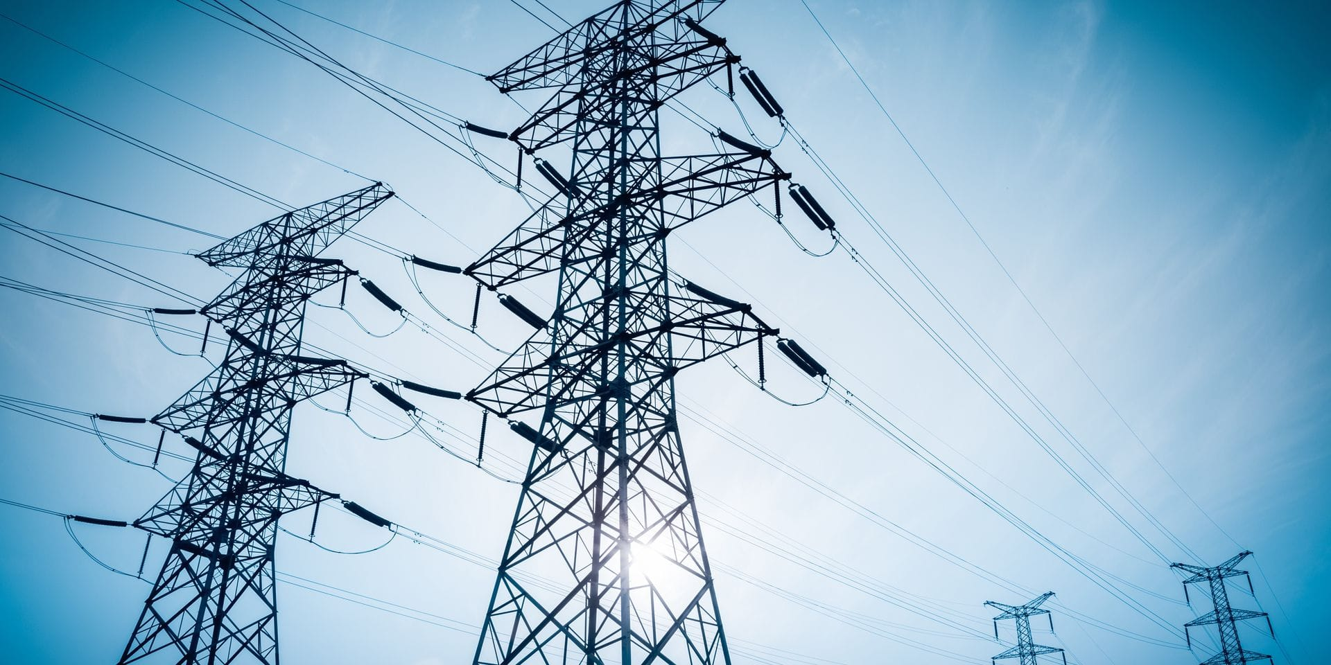 Electricity,Transmission,Pylon,Silhouetted,Against,Blue,Sky,At,Dusk