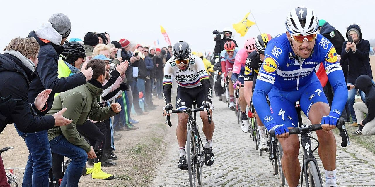 Belgium's Philippe Gilbert (R) and Slovakia's Peter Sagan ride on the Roubaix (Espace Charles Crupelant) cobbled stones sector (1) during the 117th edition of the Paris-Roubaix one-day classic cycling race, between Compiegne and Roubaix, near Bourghelles, northern France on April 14, 2019. (Photo by Stephane MANTEY / POOL / AFP)
