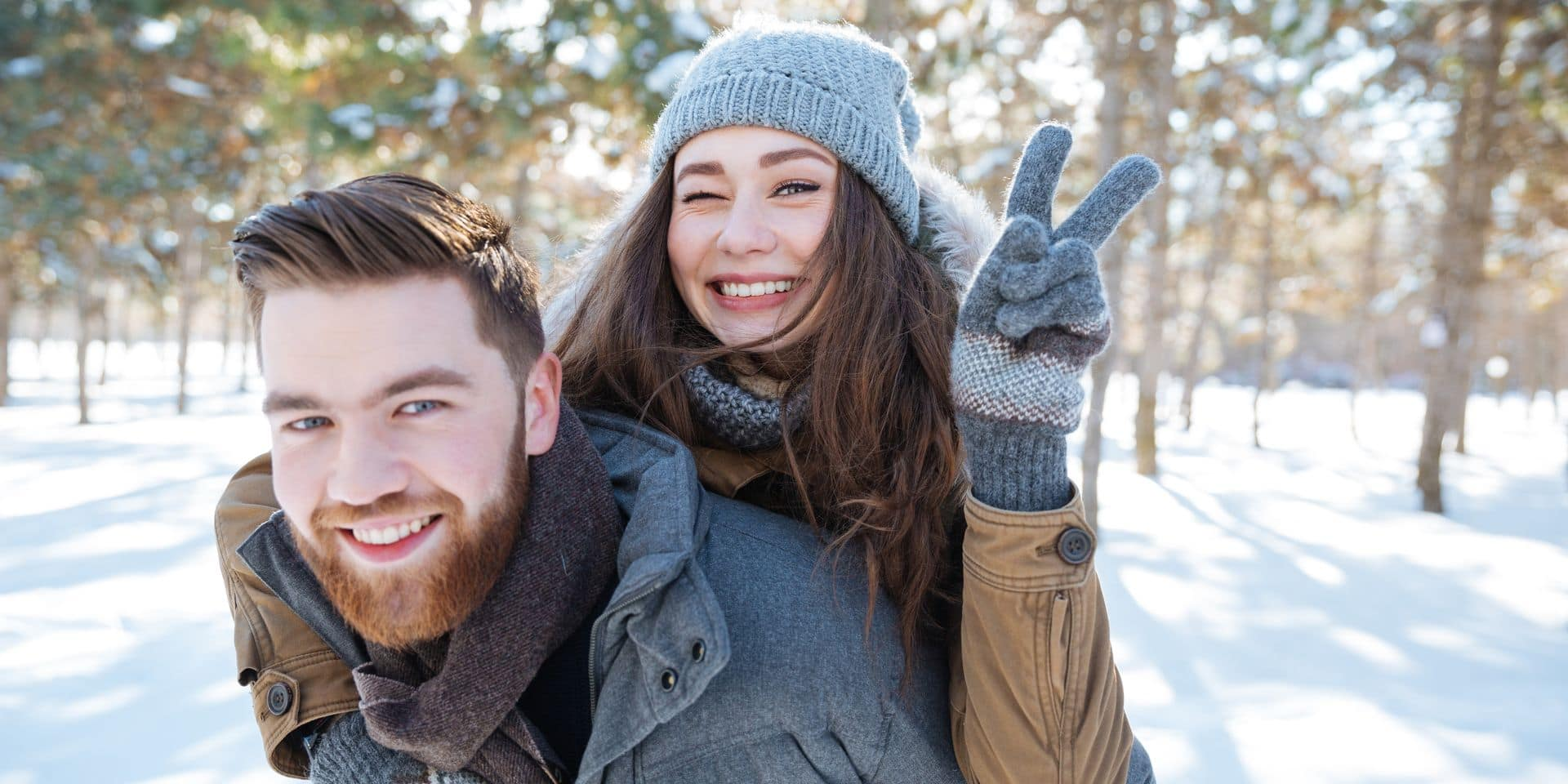 Happy,Young,Couple,Walking,In,Winter,Park,And,Showing,Victory