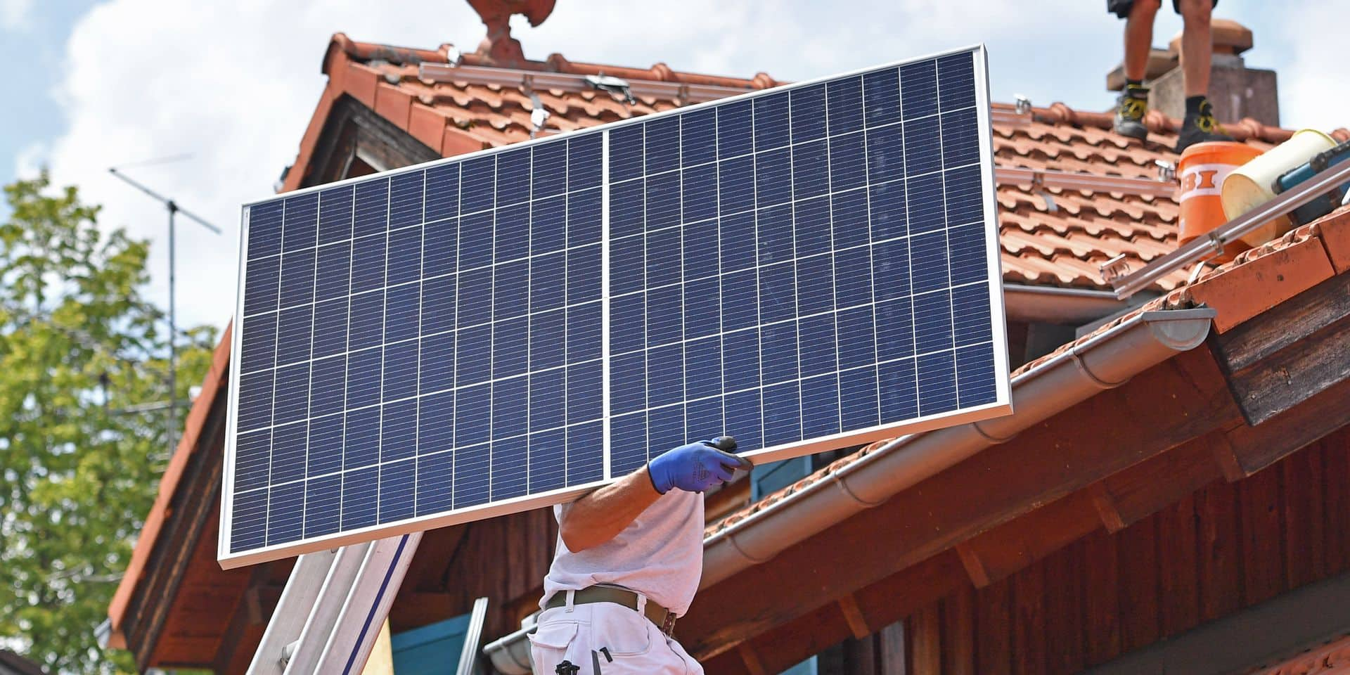 Solar modules are transported on a house roof.