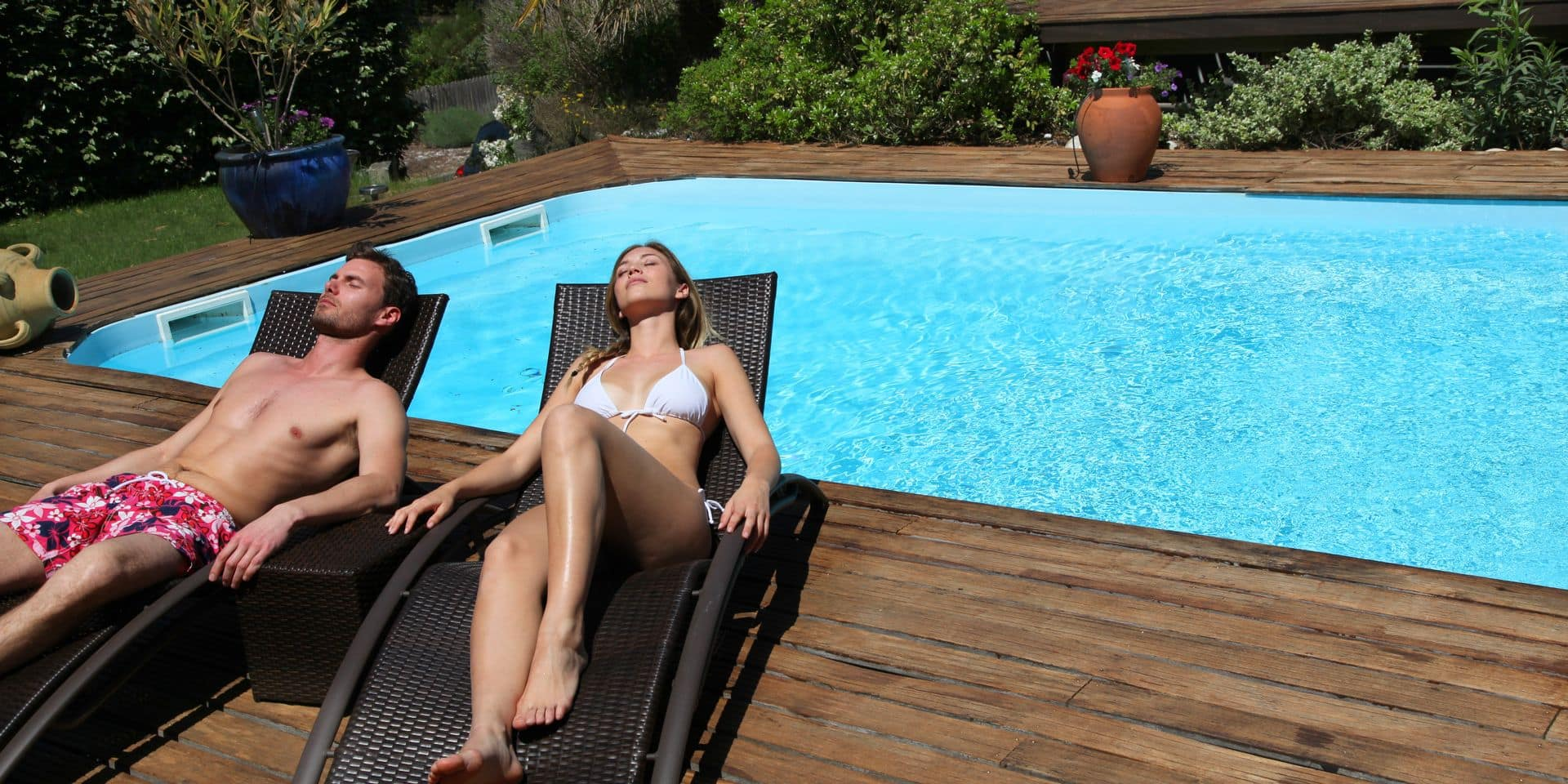 Couple,In,Long,Chairs,By,Swimming,Pool