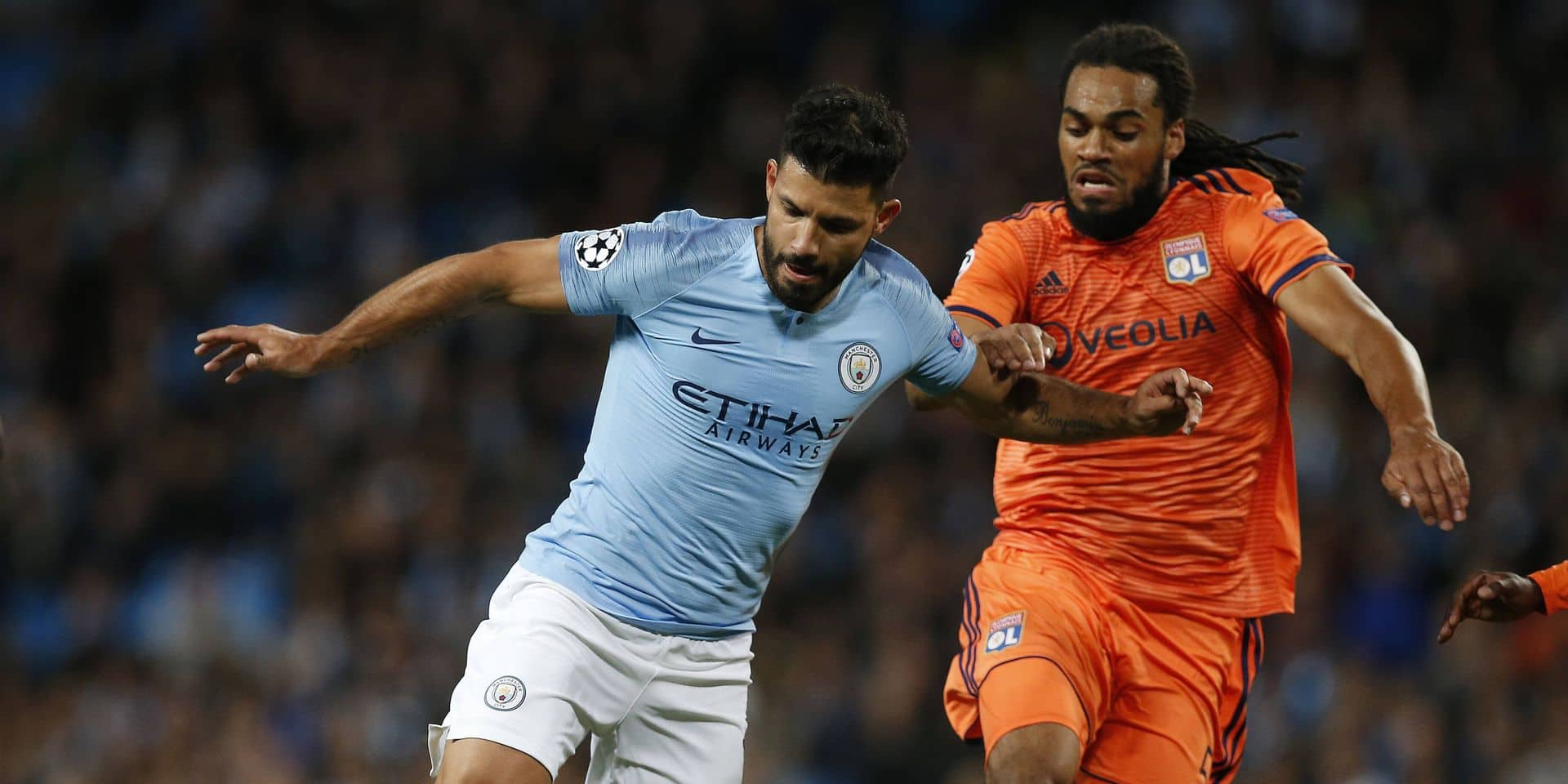 Manchester City s Sergio Aguero L is challenged by Lyon s Jason Denayer during the UEFA Champions