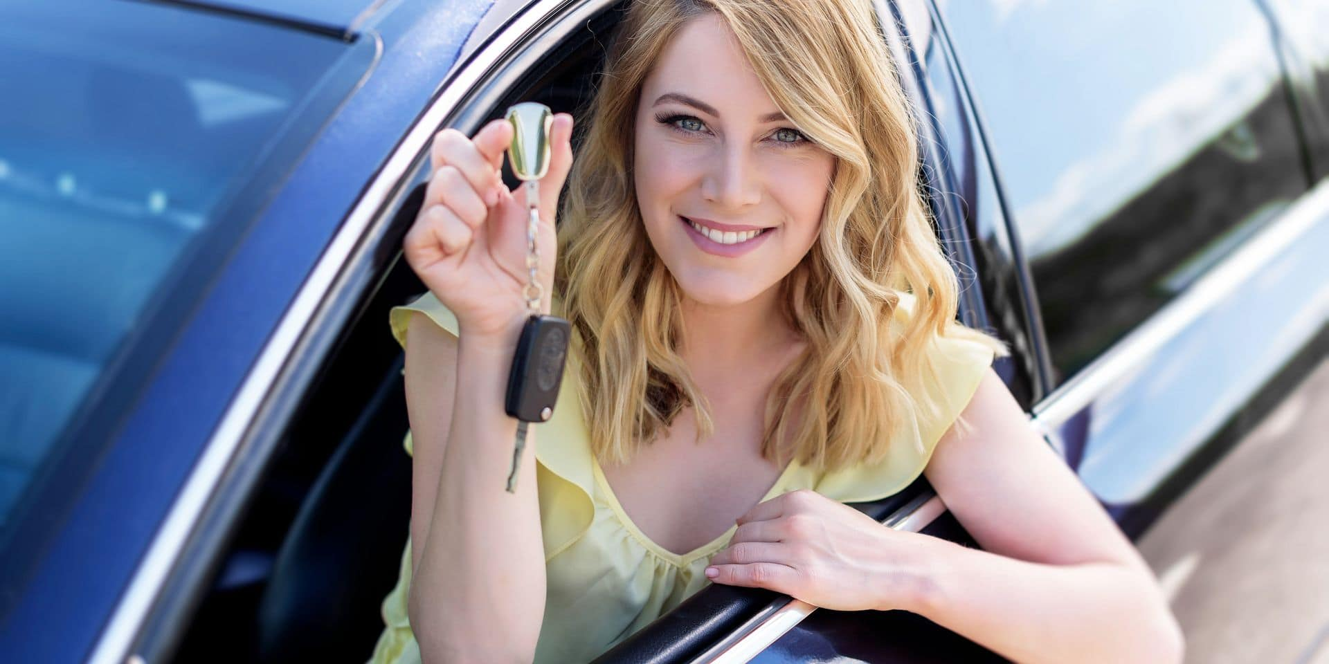 An,Attractive,Woman,In,A,Car,Holds,A,Car,Key